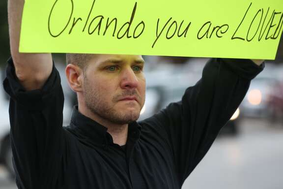 Jacob Sandler holds a sign at the corner of Montrose Rod and Westheimer Road, to show his support for the victims killed in the Orlando night club shooting, Sunday, June 12, in Houston. ( Jon Shapley / Houston Chronicle )