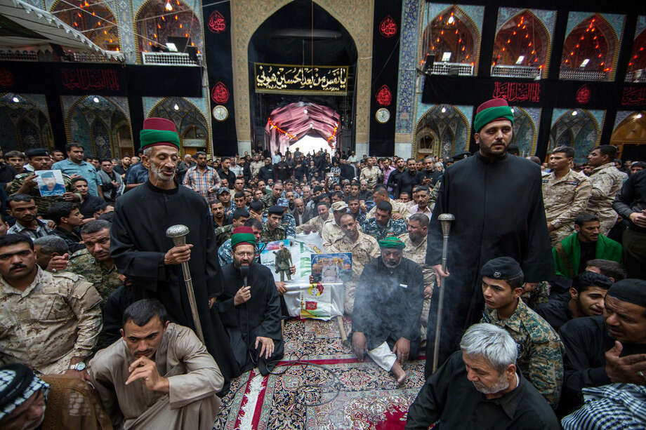 Morners pray over the coffins of members of Iraq's Special Weapons and Tactics Team (SWAT) and Shiite militiamen during their funeral procession inside the holy Shiite shrine of Imam Hussein in the Shiite holy city of Karbala, 50 miles (80 kilometers) south of Baghdad, Iraq, Monday, Oct. 27, 2014. A suicide car bomber driving a military Humvee struck a checkpoint manned by SWAT forces and Shiite militiamen in the Sunni town of Jurf al-Sakhar south of Baghdad on Monday, killing at least 24 people, officials said. (AP Photo/Ahmed al-Husseini)