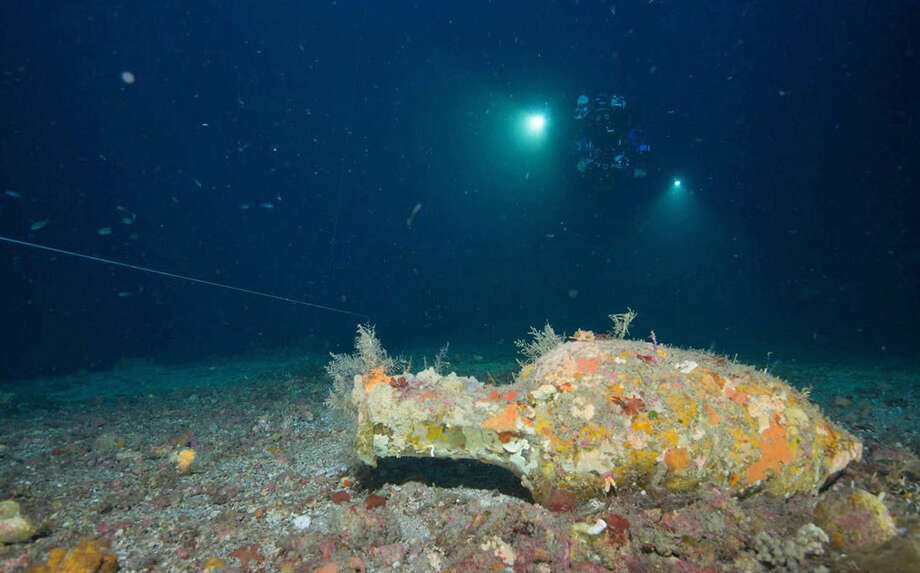 In this undated photograph provided by Global Underwater Explorers, divers illuminate Greco-Roman artifacts of a ship that sunk during the Punic Wars between 218-201 B.C., in the Mediterranean Sea, off the Aeolian Island of Panarea near Italy. The technical divers, trained in Florida's labyrinth of underwater caves, descended 410 feet to the wreck site to retrieve many of the ancient artifacts. (AP Photo/GUE, Ingemar Lundgren)