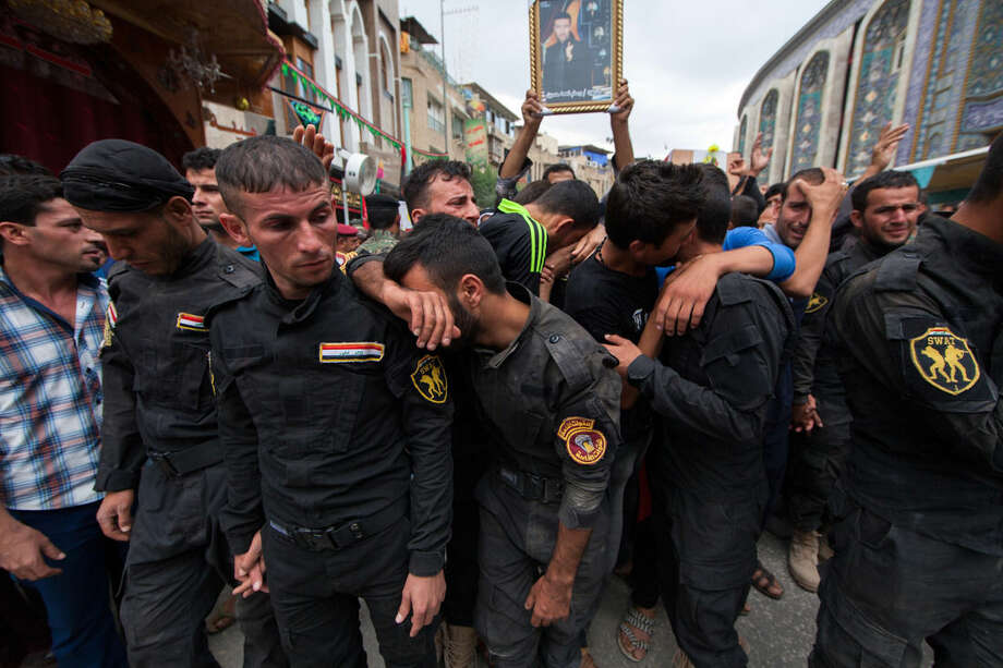 Members of Iraq's Special Weapons and Tactics Team (SWAT) mourn during the funeral procession their colleagues in the Shiite holy city of Karbala, 50 miles (80 kilometers) south of Baghdad, Iraq, Monday, Oct. 27, 2014. A suicide car bomber driving a military Humvee struck a checkpoint manned by SWAT forces and Shiite militiamen in the Sunni town of Jurf al-Sakhar south of Baghdad on Monday, killing at least 24 people, officials said. (AP Photo/Ahmed al-Husseini)