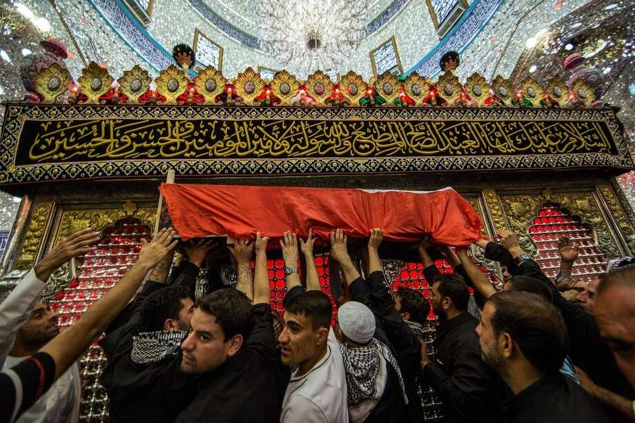 Mourners carry the flag-draped coffin of a Shiite militiaman during his funeral procession inside the holy Shiite shrine of Imam Hussein in the Shiite holy city of Karbala, 50 miles (80 kilometers) south of Baghdad, Iraq, Monday, Oct. 27, 2014. A suicide car bomber driving a military Humvee struck a checkpoint manned by Iraqi troops and pro-government Shiite militiamen in the Sunni town of Jurf al-Sakhar south of Baghdad on Monday, killing at least 24 people, officials said. (AP Photo/Ahmed al-Husseini)