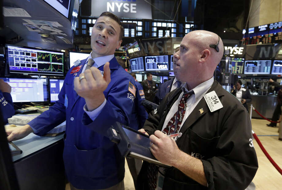 Specialist Joseph Mastrolia, left, works with traders on the floor of the New York Stock Exchange Monday, Oct. 27, 2014. U.S. stocks fell in early trading on disappointing economic news from Europe and lower oil prices. (AP Photo/Richard Drew)