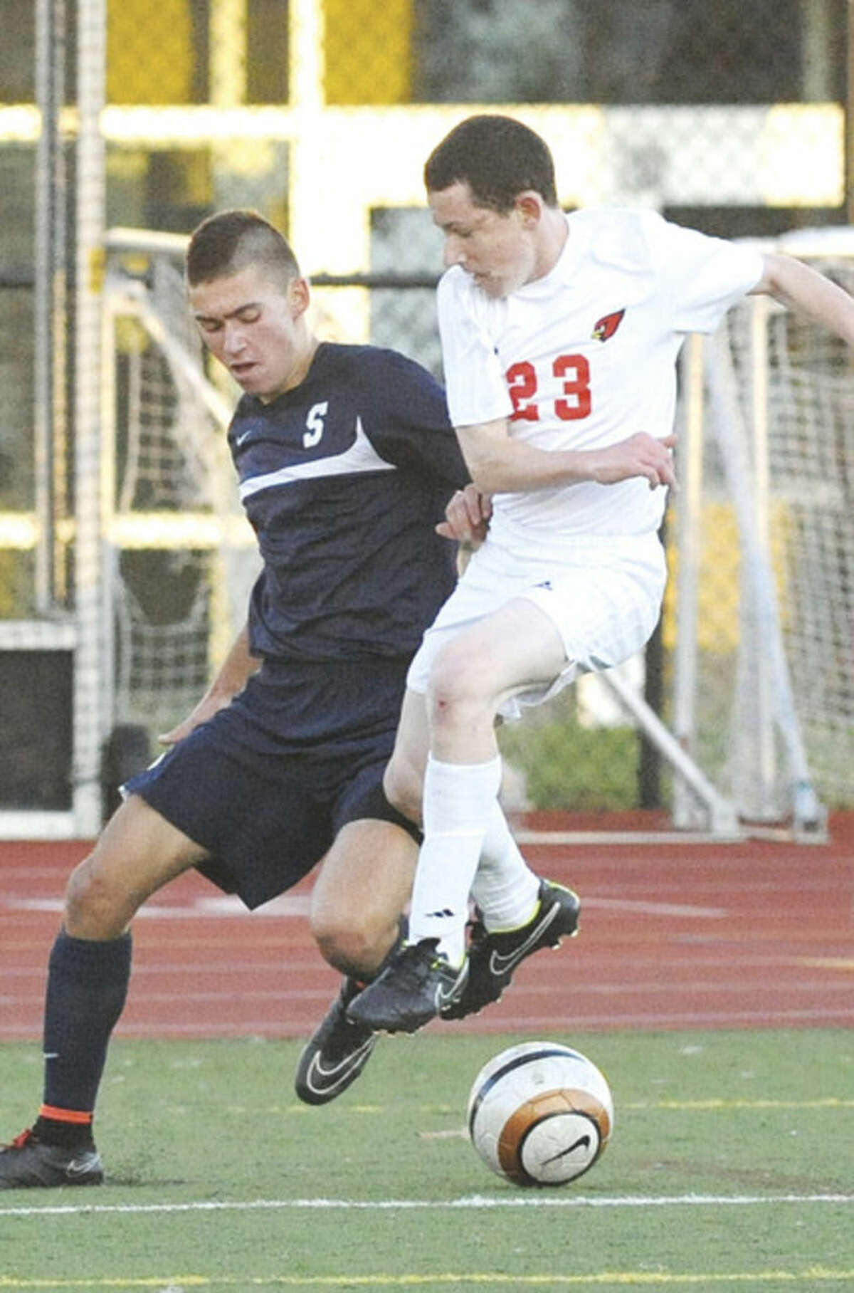 Hour photo/Matthew Vinci Staples' Nate Argosh, left, fights Greenwich's Zachary Friedman for possession during Monday afternoon's game.