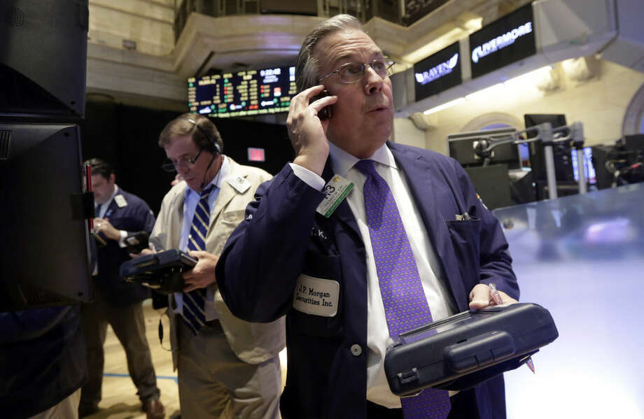 Trader Thomas Kay, right, works on the floor of the New York Stock Exchange Monday, Oct. 27, 2014. U.S. stocks fell in early trading on disappointing economic news from Europe and lower oil prices. (AP Photo/Richard Drew)
