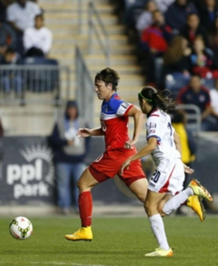 United States forward Abby Wambach moves past Costa Rica defender Wendy Acosta (20) to set up a goal in the second half during the CONCACAF championship soccer match in Chester, Pa., Sunday, Oct. 26, 2014. The United States defeated Costa Rica 6-0. (AP Photo/Rich Schultz)