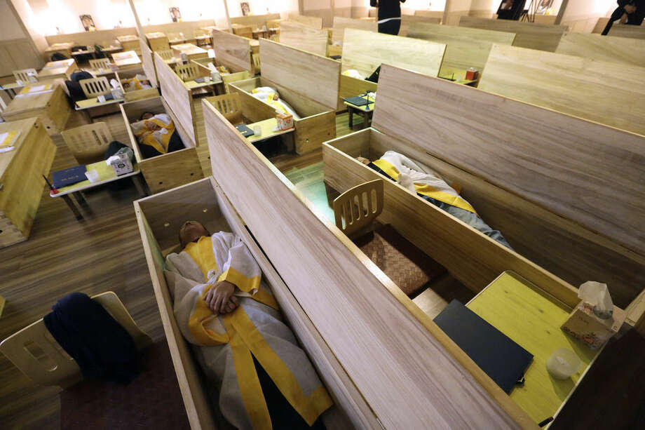 "Participants dressed in shrouds lie down inside wooden coffins during the ""death experience"" program at Hyowon Healing Center in Seoul, South Korea, Tuesday, Dec. 22, 2015. In a dark, dimly-lit room, people dressed in white burial shrouds sit down next to dozens of coffins. They write their wills, climb into the caskets, lie down and a symbolic ""angel of death"" _ a man wearing a traditional Korean hat and black robes -- shuts the lid of each casket.(AP Photo/Ahn Young-joon)"