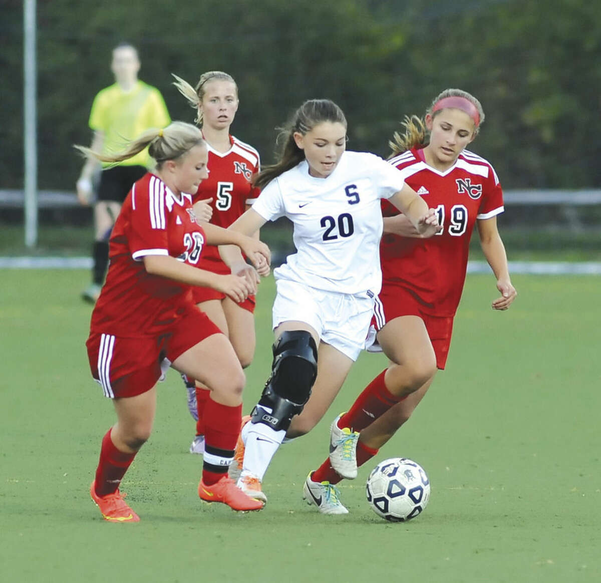 Hour photo/John Nash Staples' Anne Amacker (20) keeps control of the ball while surrounded by New Canaan players, from left, Courtney Overacker, Braeden Dial, and Katharine Kuchinski during Monday's FCIAC semifinal played at Kristine Lilly Field in Wilton. Staples won, 4-0, to advance to its first FCIAC title game since 1995.