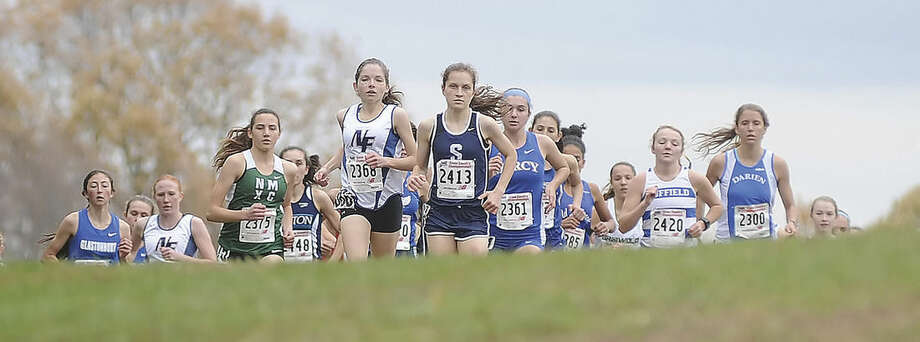 Hour photo/John NashStaples High School junior Hannah DeBalsi (2413) leads a pack of runners up the hill following the start of Friday's State Open cross country championship meet at Wickham Park in Manchester. DeBalsi won her second straight State Open title, breaking her own course record with a time of 17:59.