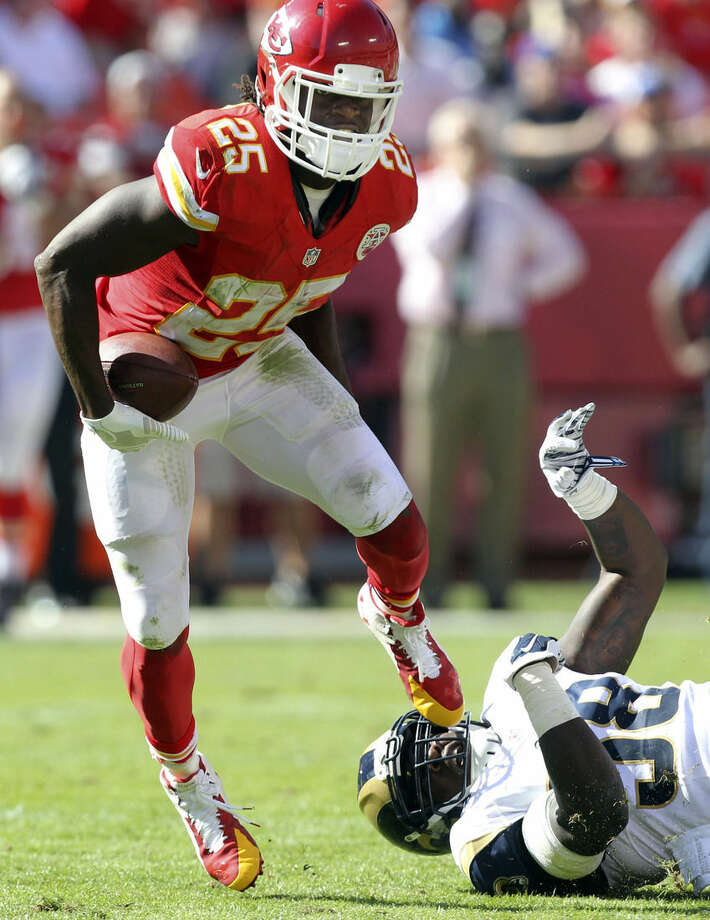 Kansas City Chiefs running back Jamaal Charles (25) breaks a tackle by St. Louis Rams outside linebacker Jo-Lonn Dunbar (58) in the second half of an NFL football game in Kansas City, Mo., Sunday, Oct. 26, 2014. (AP Photo/Ed Zurga)