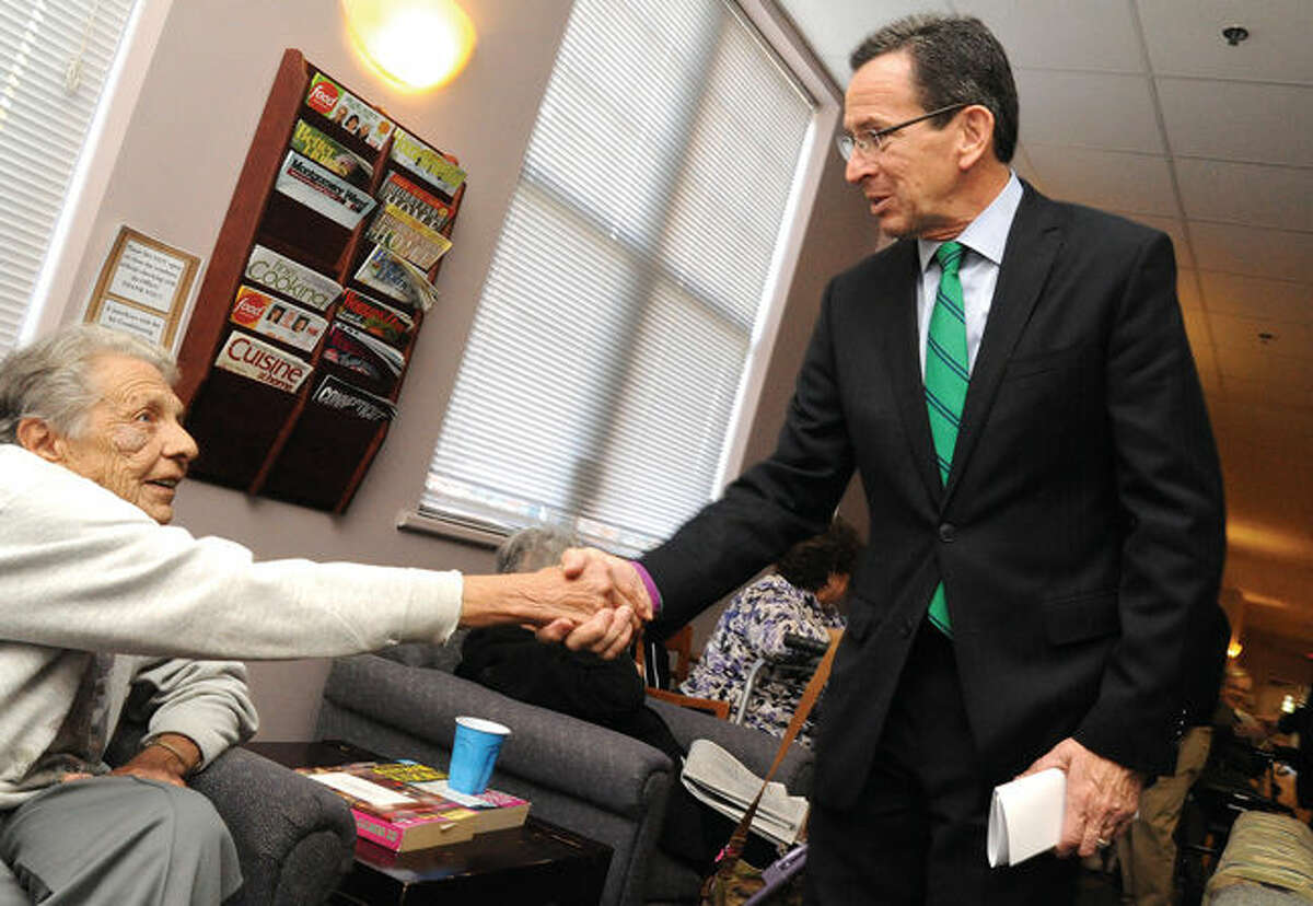 Gov. Dannel P. Malloy greets Barbara Dunlap at the senior center Monday as he campaigns at Marvin Center in Norwalk.