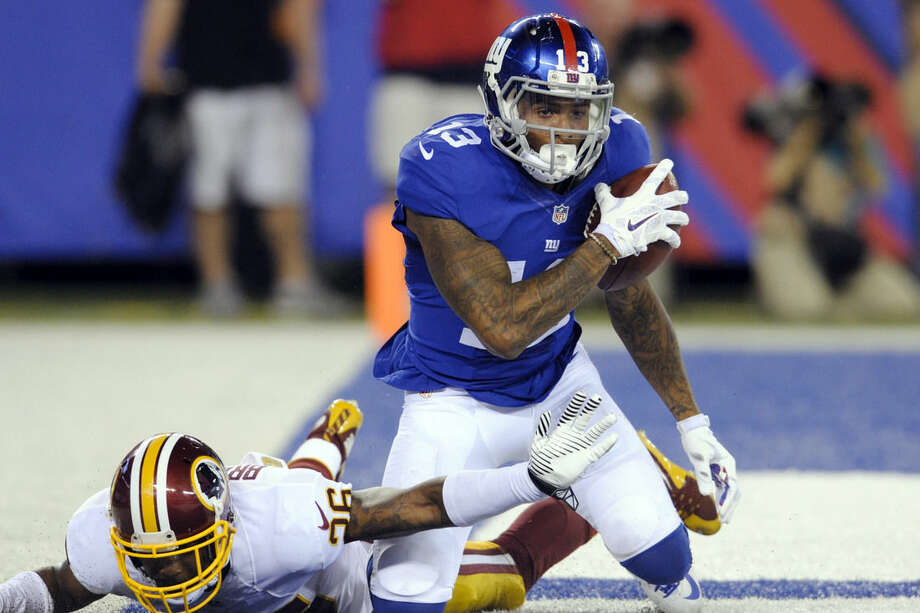 FILE - In this Sept. 24, 2015, file photo, New York Giants wide receiver Odell Beckham Jr. (13) celebrates as Washington Redskins' Bashaud Breeland (26) reaches for him after Beckham scored a touchdown during the second half an NFL football game in East Rutherford, N.J. The Giants head into the final two weeks of the season not sure whether Beckham will be eligible to play against Minnesota next weekend because of his helmet to helmet hit on Carolina Panthers' Josh Norman. (AP Photo/Bill Kostroun, File)