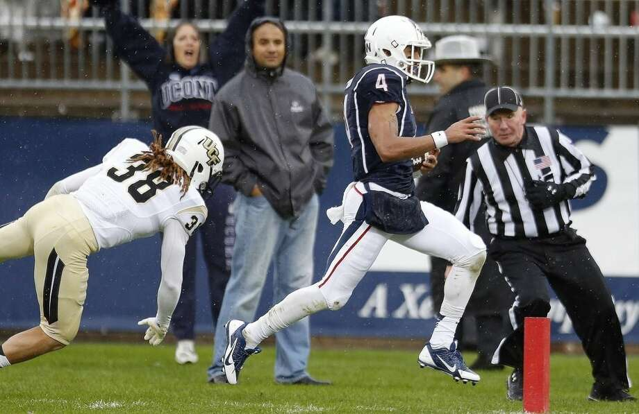 Connecticut wide receiver Deshon Foxx (4) carries the ball into the end zone in front of Central Florida defensive back Jordan Ozerities (38) during the second quarter of an NCAA college football game in East Hartford, Conn., Saturday, Nov. 1, 2014. (AP Photo/Michael Dwyer)