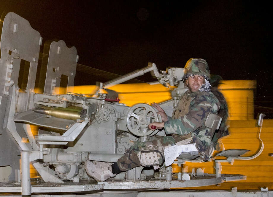 An Iraqi Kurdish peshmerga fighter rides on an artillery weapon as he leaves the outskirts of Suruc, Turkey, towards the Turkey-Syria border, on the way to the Syrian city of Kobani, Friday, Oct. 31, 2014. The 10 peshmerga fighters from Iraq who entered the embattled northern Syrian town of Kobani one day earlier returned to Turkey Friday to prepare for their forces' full deployment, and a senior Kurdish official blamed Ankara for the delay. (AP Photo/Vadim Ghirda)