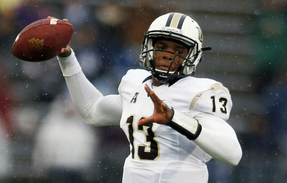 Central Florida quarterback Justin Holman passes in the first quarter of an NCAA college football game against Connecticut in East Hartford, Conn., Saturday, Nov. 1, 2014. (AP Photo/Michael Dwyer)