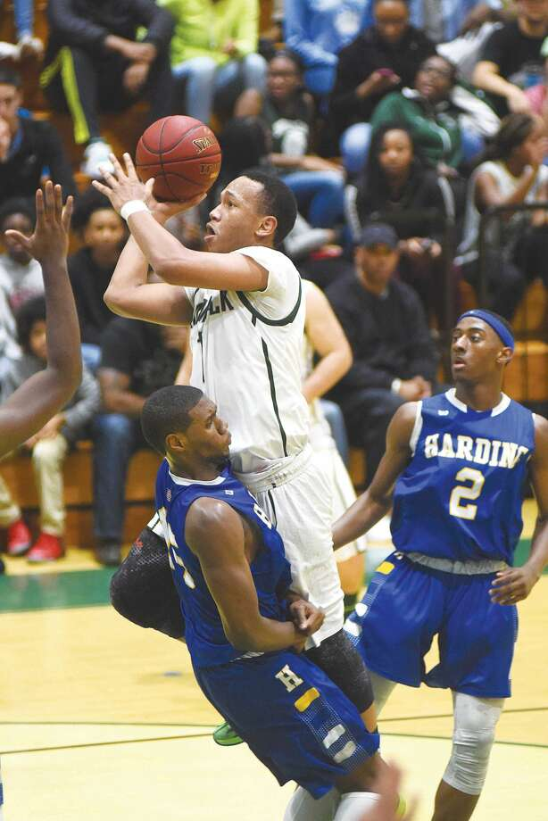 Hour photo/John Nash - Norwalk's A.J. Jerome, center, crashes into Harding's Calvin Seward on a charge call as the Presidents' TJ Pettway looks on.