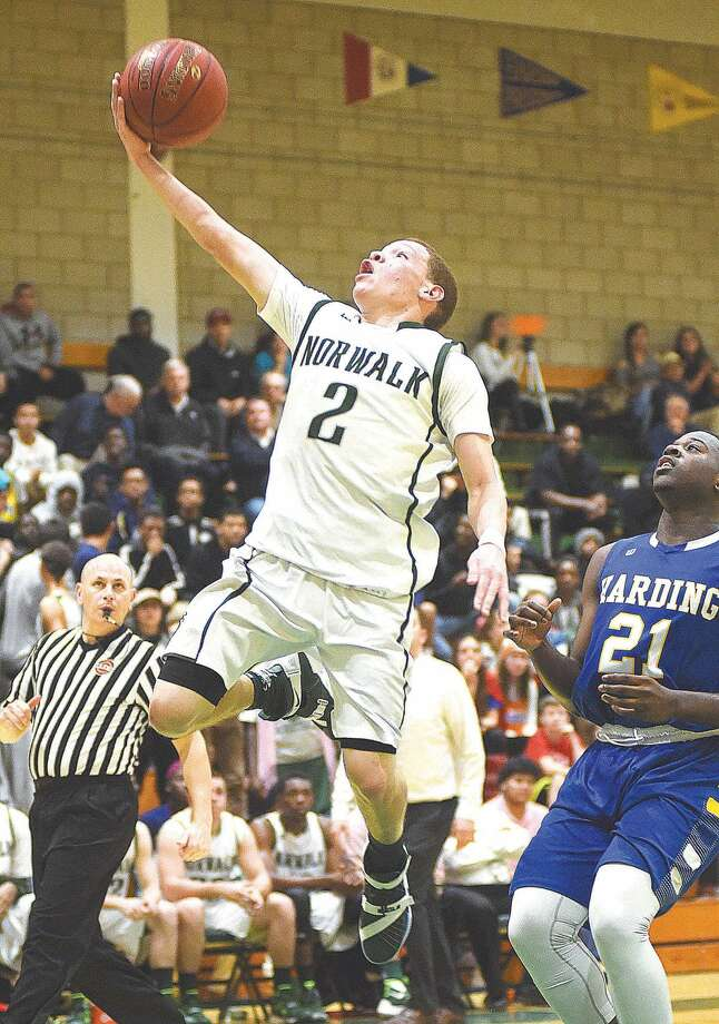 Hour photo/John Nash - Norwalk's Mark Crafter takes the ball up for a layup during the second half of Tuesday's season-opening game against Harding.