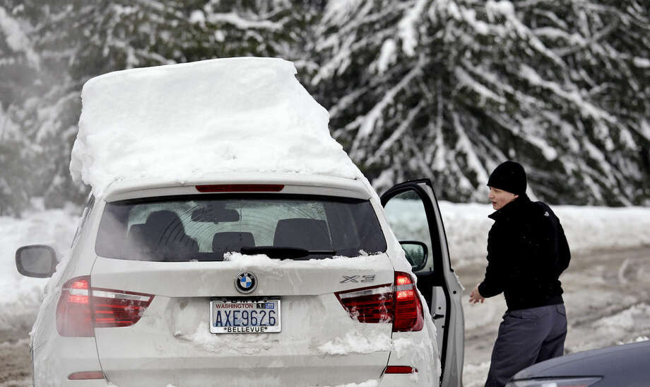 Siri Bryant, of Sammamish, Wash., gets into her car, still covered with a couple of feet of snow after being parked overnight at Snoqualmie Pass, Wash., Tuesday, Dec. 22, 2015. A weather pattern that could be associated with El Nino has turned winter upside-down across the U.S. during a week of heavy holiday travel, bringing spring-like warmth to the Northeast, a risk of tornadoes in the South and so much snow in parts of the West that there are concerns about avalanches. On Christmas Day, it could be warmer in New York City than Los Angeles.(AP Photo/Elaine Thompson)