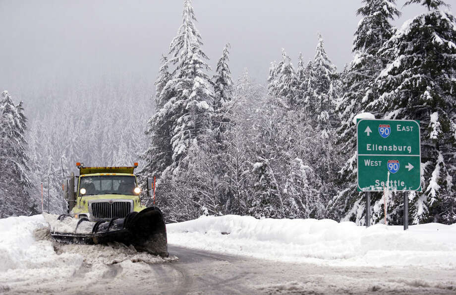 A snowplow clears an overpass of freshly-fallen snow over Interstate 90 at Snoqualmie Pass, Wash., Tuesday, Dec. 22, 2015. A weather pattern that could be associated with El Nino has turned winter upside-down across the U.S. during a week of heavy holiday travel, bringing spring-like warmth to the Northeast, a risk of tornadoes in the South and so much snow in parts of the West that there are concerns about avalanches. On Christmas Day, it could be warmer in New York City than Los Angeles.(AP Photo/Elaine Thompson)