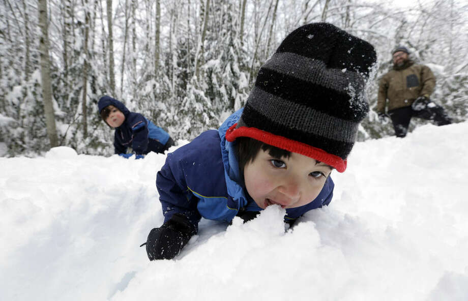Leon Perkins, 3, leans forward to take a bite of snow as he plays with his brother Conner, left, 2, and his father Erin, Tuesday, Dec. 22, 2015, at Snoqualmie Pass, Wash. The Seattle family headed to the mountains Tuesday to enjoy the new snow that fell overnight. A weather pattern that could be associated with El Nino has turned winter upside-down across the U.S. during a week of heavy holiday travel, bringing spring-like warmth to the Northeast, a risk of tornadoes in the South and so much snow in parts of the West that there are concerns about avalanches. On Christmas Day, it could be warmer in New York City than Los Angeles.(AP Photo/Elaine Thompson)