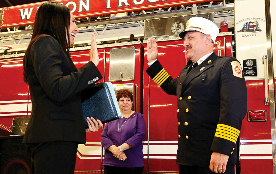Wilton Fire Chief Ronald Kanterman is sworn in by Wilton Town Clerk Laurie Kaback, as Kanterma's wife, Kay, looks on during a ceremony at fire headquarters Friday.