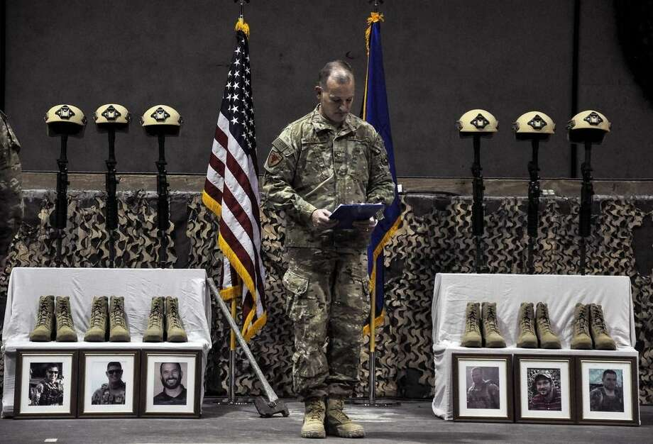 A U.S. Air Force officer speaks during a memorial ceremony for six Airmen killed in a suicide attack, at Bagram Air Field, Afghanistan on Wednesday, Dec. 23, 2015. The deadliest attack in Afghanistan since 2013 killed six U.S. troops on Monday, including a family man from Long Island, New York; a South Texan; a New York City police detective; a Georgia high school and college athlete; an expectant father from Philadelphia; and a major from suburban Minneapolis with ties to the military's LGBT community. They were killed when their patrol was attacked by a suicide bomber on a motorcycle near Bagram Air Base, the Defense Department said. (Tech. Sgt. Robert Cloys/U.S. Air Force via AP)