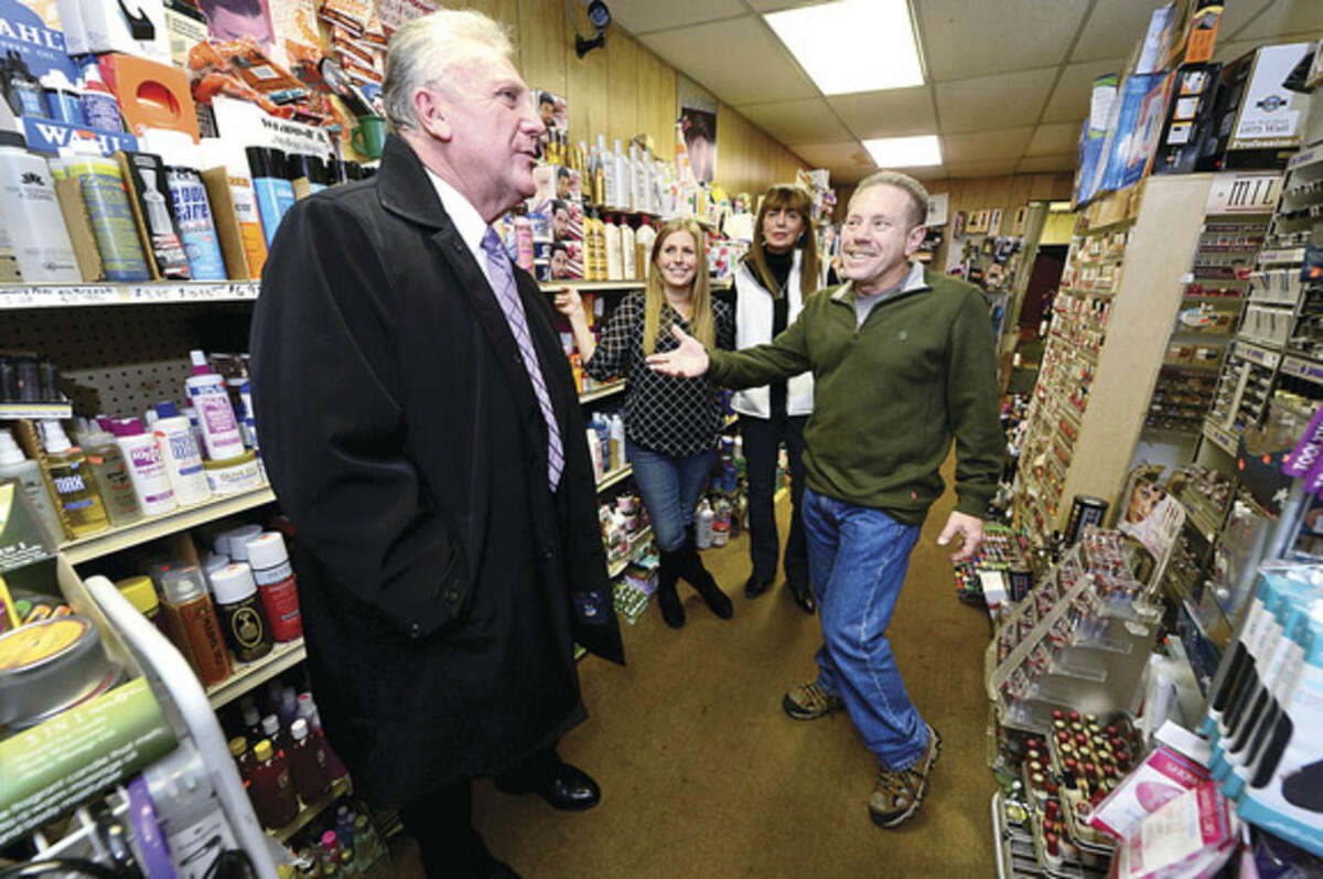 Hour photo / Erik Trautmann Norwalk Mayor Harry Rilling visits with the owners of Norwalk Beauty Supply, Bob and Nancy Benick and their daughter Kim Hellthaler, as part of a new initiative to promote small businesses.
