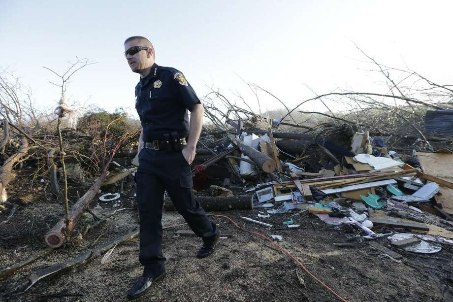 Interim Sheriff Nick Weems of the Perry County Sheriff's Department looks over debris Thursday, Dec. 24, 2015, near Linden, Tenn. Several people were killed in Mississippi, Tennessee and Arkansas as spring-like storms mixed with unseasonably warm weather spawned rare Christmastime tornadoes in the South. (AP Photo/Mark Humphrey)