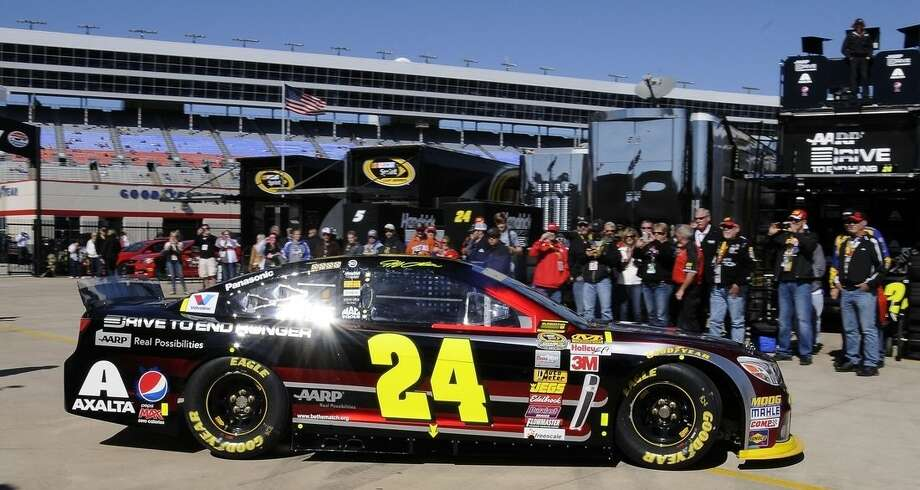 NASCAR fans watch driver Jeff Gordon (24) pull out of the garage during practice for Sunday's NASCAR Sprint Cup series auto race at the Texas Motor Speedway in Fort Worth, Texas, Saturday, Nov. 1, 2014. (AP Photo/Larry Papke)