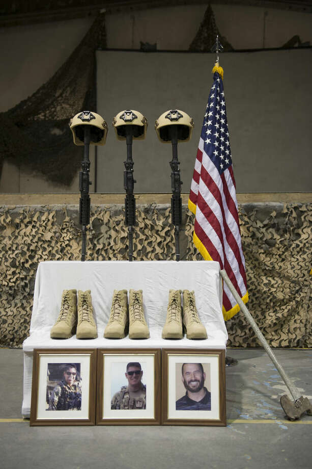 Helmets, rifles and boots represent three fallen U.S. Airmen during their memorial ceremony for six Americans killed in a suicide attack, at Bagram Air Field, Afghanistan on Wednesday, Dec. 23, 2015. The deadliest attack in Afghanistan since 2013 killed six U.S. troops on Monday, including a family man from Long Island, New York; a South Texan; a New York City police detective; a Georgia high school and college athlete; an expectant father from Philadelphia; and a major from suburban Minneapolis with ties to the military's LGBT community. They were killed when their patrol was attacked by a suicide bomber on a motorcycle near Bagram Air Base, the Defense Department said. (Tech. Sgt. Robert Cloys/U.S. Air Force via AP)