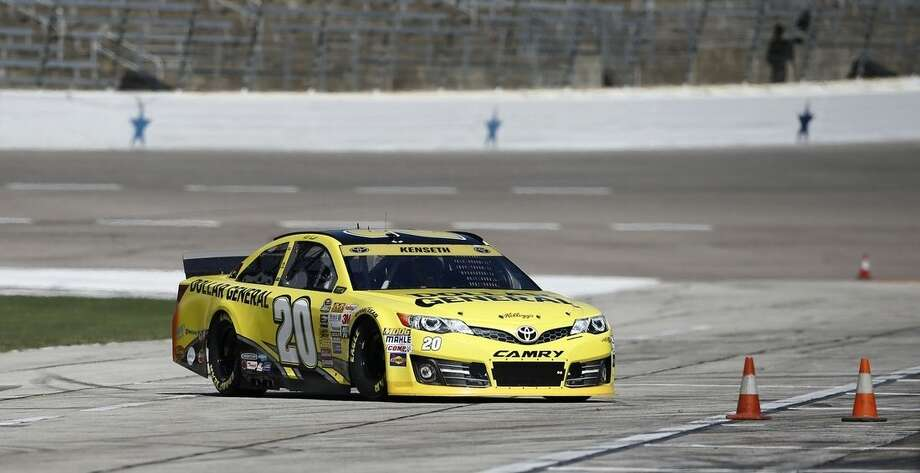 Driver Matt Kenseth (20) pulls into the pit area during practice for Sunday's NASCAR Sprint Cup series auto race at the Texas Motor Speedway in Fort Worth, Texas, Saturday, Nov. 1, 2014. (AP Photo/Jim Cowsert)