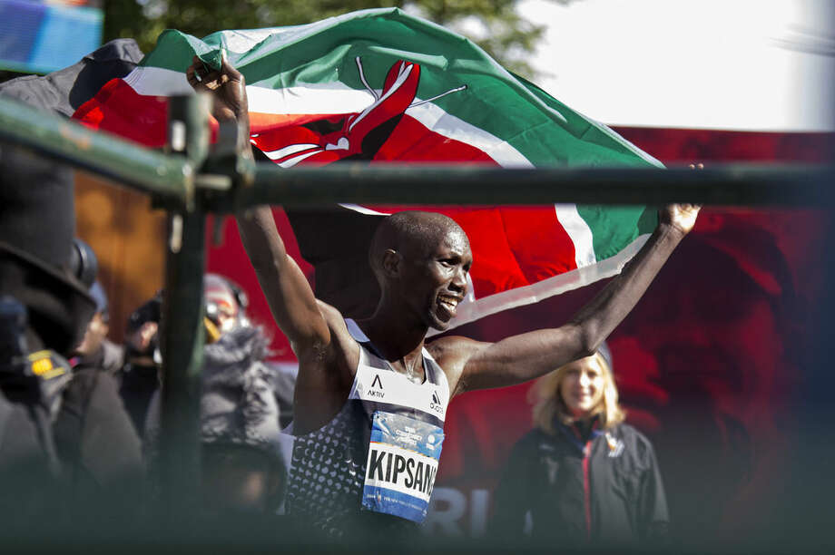 Wilson Kipsang of Kenya hoists his country's flag after winning the New York City Marathon in New York Sunday, Nov. 2, 2014. Kipsang won in an unofficial time of 2 hours, 10 minutes, 59 seconds. (AP Photo/Craig Ruttle)