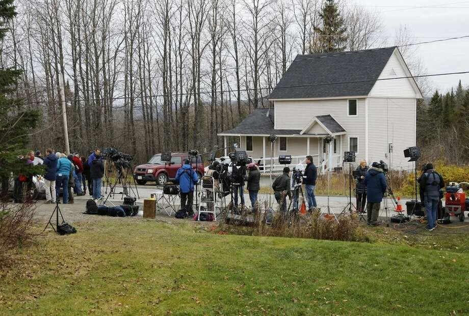 Reporters keep watch across from nurse Kaci Hickox's house, Friday, Oct. 31, 2014, in Fort Kent, Maine. Maine health officials have asked a court to limit the movements of nurse Kaci Hickox, who defied a voluntary quarantine for medical workers who have treated Ebola patients. Officials filed documents Thursday, following through with a threat to try to isolate her. ( AP Photo/Robert F. Bukaty)