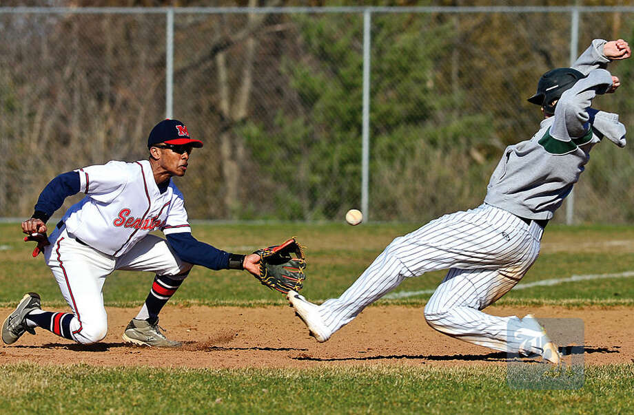 Hour photo / Erik Trautmann Brien McMahon second baseman Edwin Odwolo tries to get a tag on Norwalk High School's #7 Mike Gonzalez in their intra city baseball game at Brien Mcmahon High School Saturday.