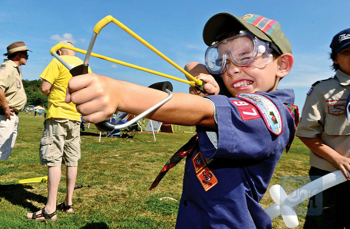 Hour photo / Erik Trautmann Pack 97 cub scout Stephen Artale trakes target prctice with a wrist rocket sling shot during the 'Norwalk Scouting Adventure' at Taylor Farm in Norwalk Saturday.