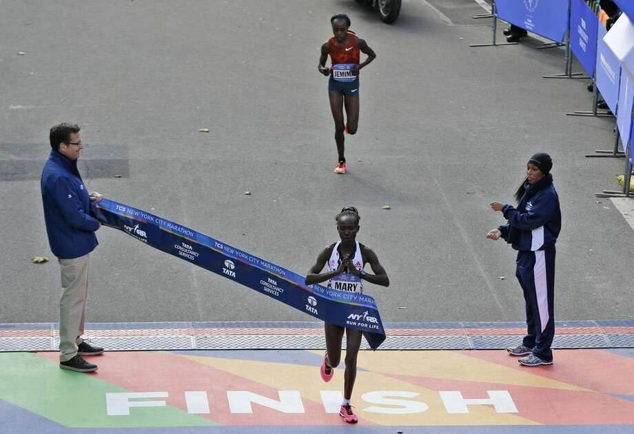 Mary Keitany, of Kenya, crosses the finish line first, in front of Jemima Sumgong, of Kenya, in the women's division at the 2014 New York City Marathon in New York, Sunday, Nov. 2, 2014. (AP Photo/Seth Wenig)