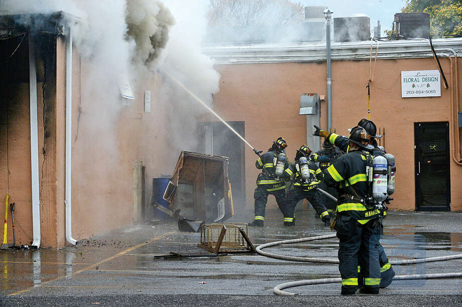Hour photo / Erik Trautmann Norwalk firefighters battle a blaze that engulfed Ludlow Shopping Center in East Norwalk Thursday afternoon.