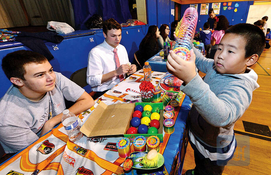 Hour photo / Erik Trautmann Gavin McCallum, Matt Cavanagh and other students in the entrepreneurship program at Norwalk High School sell items to students at Naramake Elementary School including 2nd grader Terry Yang.