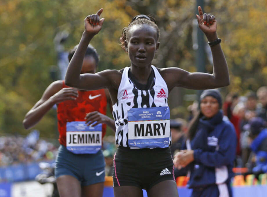 Mary Keitany celebrates as she edges out Jemima Sumgong, both of Kenya, after the pair finished first and second in the women's division of the 44th annual New York City Marathon in New York, Sunday, Nov. 2, 2014. (AP Photo/Kathy Willens)
