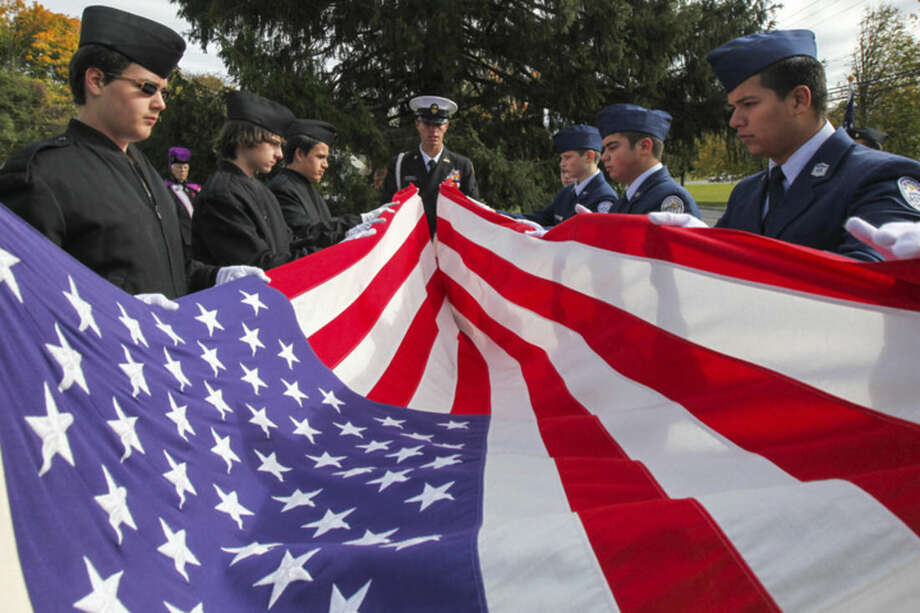 Hour photo/Chris Palermo. Norwalk High and Brien McMahon ROTC Cadets fold up the flag for World War II Marine Matthew Charles Vinci, who was the last vet to be honored at the Veteran of the month ceremony Sunday morning at the American Legion Post 12.