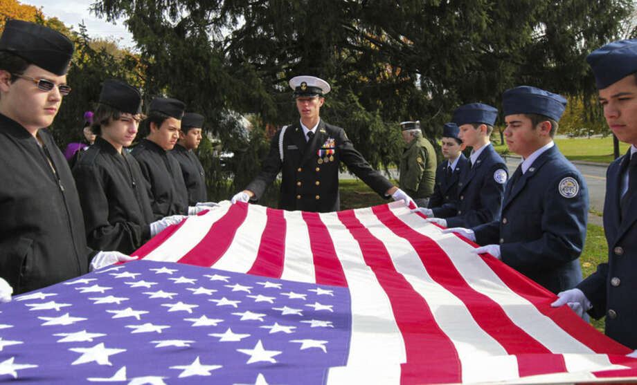 Hour photo/Chris PalermoNorwalk High and Brien McMahon ROTC Cadets fold up the flag for World War II Marine Matthew Charles Vinci, who was the last vet to be honored at the Veteran of the month ceremony, Sunday morning at the American Legion.