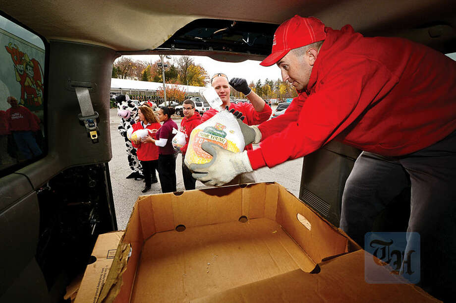 "Hour photo / Erik Trautmann Peter Tournas gets handed a frozen turkey from fellow employee, Mike Coates, as Stew Leonard's continues it's long-standing tradition of giving back to the communities it serves with its 36th Annual ""Turkey Brigade"" in Norwalk Thursday. 2,190 turkeys for Thanksgiving were distributed to more than 100 organizations serving those in need in Norwalk, Newington and Danbury, Connecticut and in Farmingdale and Yonkers, New York."