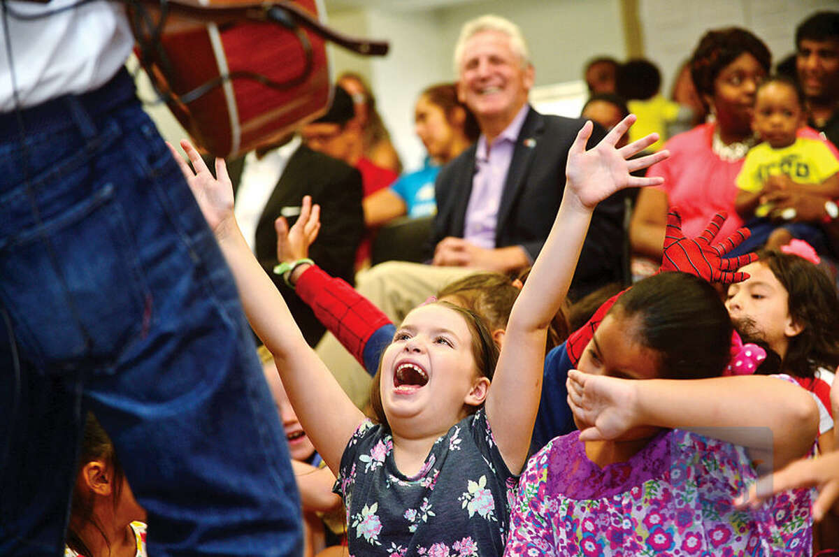 """Hour photo / Erik Trautmann Yessamin Arias, 8, sings along with Al deCant's """"Rockin' and Reading with Pete the Cat"""" performance during the Back to School Celebration for children in grades K - 5 at the SoNo Library Saturday sponsored by the library and ConnCAN (The Connecticut Coalition for Achievement Now)."""