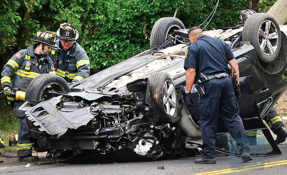 Hour photo / Erik Trautmann Norwalk emergency personnel work to free the driver of a volkswagon sedan that rolled over on Newtown Ave in a single-car accident Friday morning. The driver was conscious and transported to Norwalk Hospital.