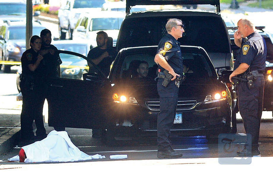 Hour photo / Erik Trautmann Norwalk police investigate the scene after a person jumped to their death from the I-95 overpass onto West Ave in Norwalk Friday afternoon.