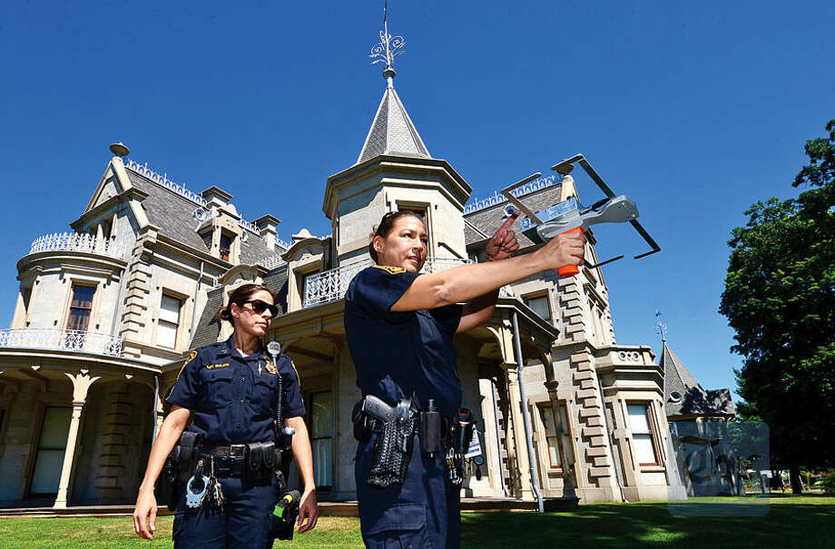 Hour photo / Erik Trautmann Norwalk police seargent Sophia Golino and officer Kelly Hollister demonstrate how their tracking device, Project Lifesaver, works at Mathews Park Thursday. As part of the demonstration Hour reporter Robin Sattler hid herself at the park after being fitted with the transmitter and the officers were able to locate her within 10 minutes.