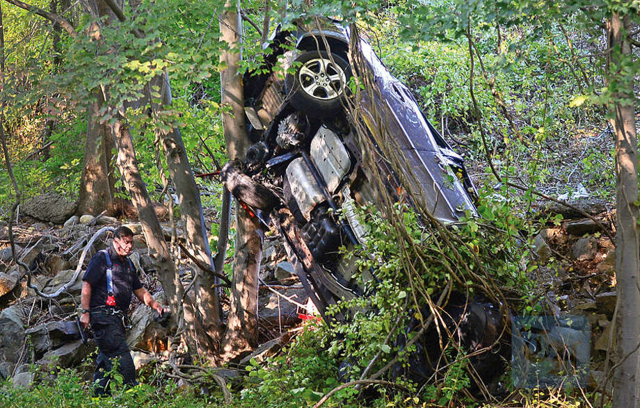 Hour photo / Erik Trautmann Emergency personnel investigate a four car accident that closed down Route 7 Southboaund late Tuesday afternoon. Several cars overturned sending one down the over the guardrail and down the Norwalk River embankment.
