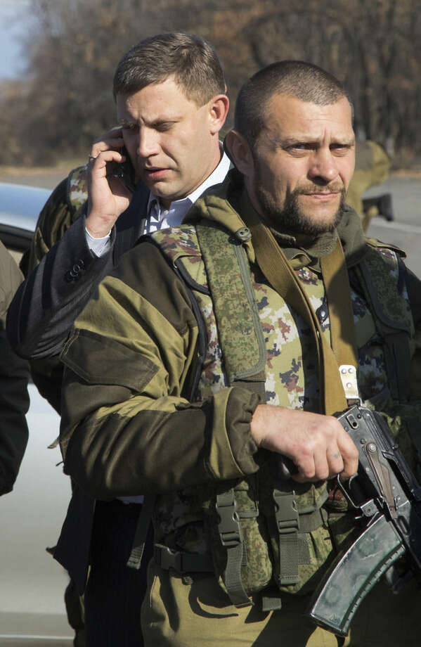 Pro-Russian rebel leader Alexander Zakharchenko, left, surrounded by his security speaks on a phone not far from the front line near Donetsk airport in the city of Donetsk, eastern Ukraine, Sunday, Nov. 2, 2014. Residents of separatist-controlled regions in eastern Ukraine voted Sunday to elect legislators and executives in polls that have been staunchly denounced by the international community. (AP Photo/Dmitry Lovetsky)