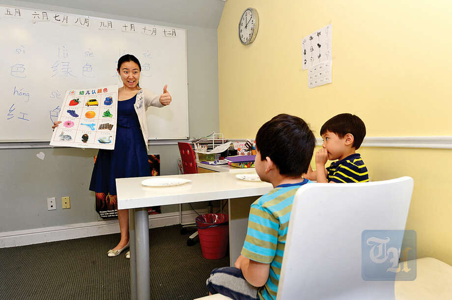 Hour photo / Erik Trautmann Wilton's Mandarin School teacher Niki Li works with students Alexander Mariani, 5, and Charles Lugo, 4, at the school Wednesday afternoon.