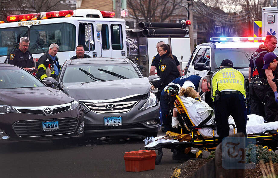Hour photo / Erik Trautmann Norwalk emergency personnel tend to an injured woman after a two car accident on Gergory Boulevard Tuesday morning.