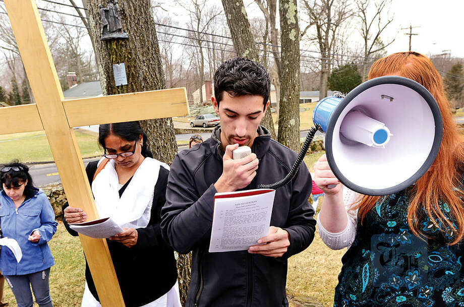 Hour photo / Erik Trautmann Parishioners of St. Matthew's Church in Norwalk including Massimo DiFrederico follow the Stations of the Cross for their annual observation of Good Friday.